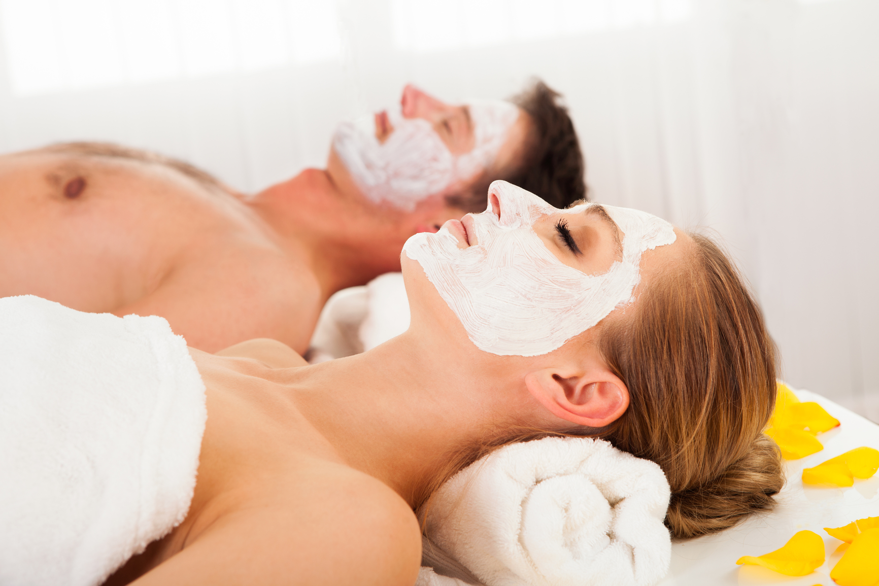 Man and woman in face masks lying back on clean white towels in a spa relaxing